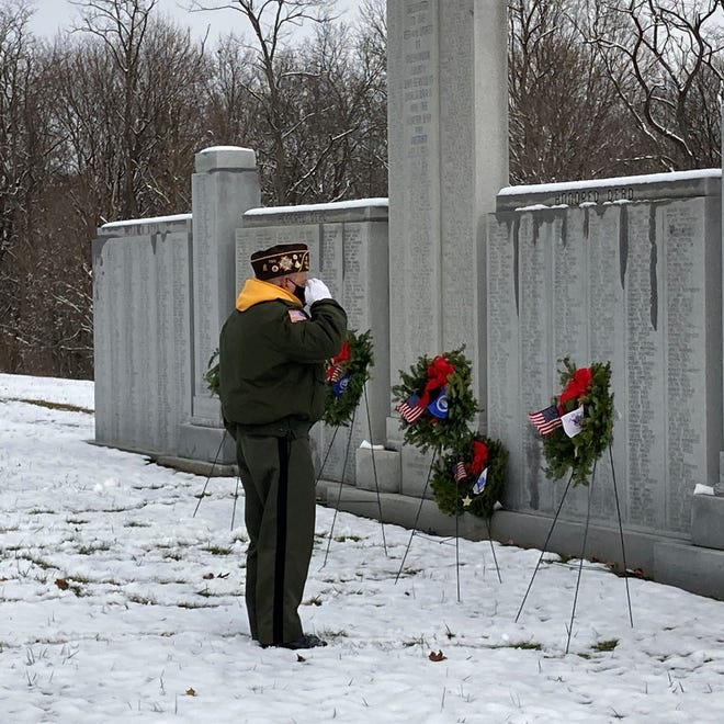 A veteran salutes those who served at Greenwood Cemetery's Veterans Memorial Wall.