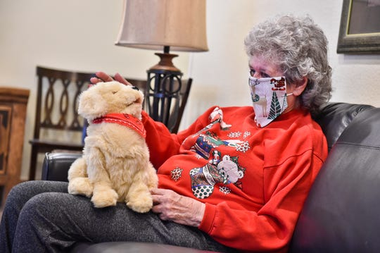 "Margie Copenhaver, an 83-year-old resident of Eagle Manor in Helena, Mont., pets her robotic pet dog Muffie. ""Muffie is good company,"" says Copenhaver. ""Muffie talks to me and I talk to her. She is a cutie."" The Helena Area Agency on Aging says money for the pets came through federal virus relief funding."