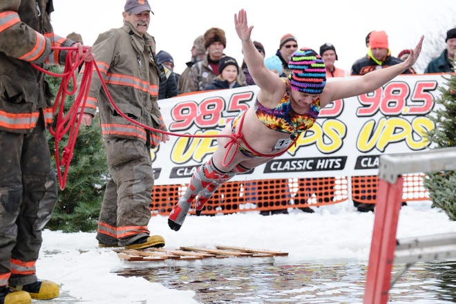 A Polar Dip contestant takes the plunge during the Tip-Up Town USA winter festival on Jan. 25 in Houghton Lake, Mich. The 2021 festival has been moved from Jan. 16-17 to Feb. 27-28 because of coronavirus restrictions on attendance at outdoor events.