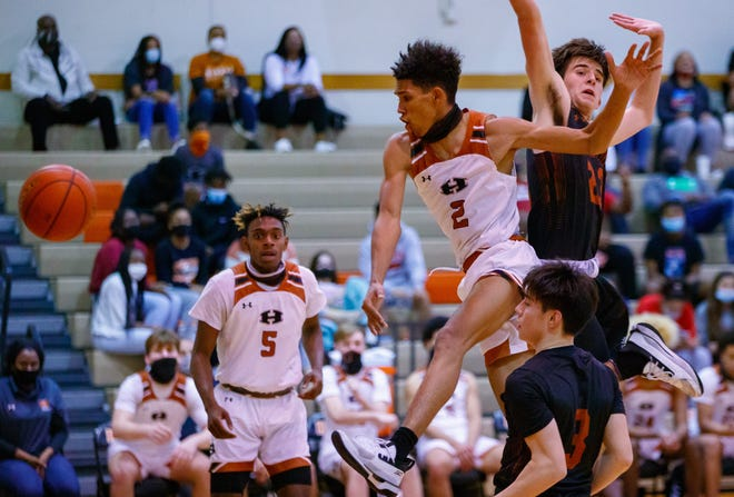 Hutto Hippos guard Jailen Bedford, center, leaps for the shot and is fouled by Westwood Warriors center Carson King, right, during the fourth period at the District 25-6A boys basketball game on Tuesday at Hutto High School.