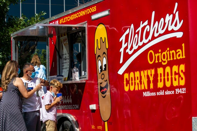 Roman DeLeon and his son Michael, 9, receive their order at the Fletcher's Corny Dogs popup food truck at Mutts Canine Cantina in Dallas in July. The Fletcher family has reached agreement in a dispute over a business name.