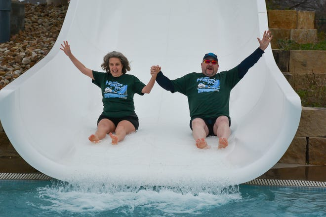 Lisa and David Rogers hold hands as they go down the slide during the city's 9th annual Pfreeze Pflop on New Year's Day at the Scott Mentzer Pool. This year, COVID-19 protocols will be put in place.