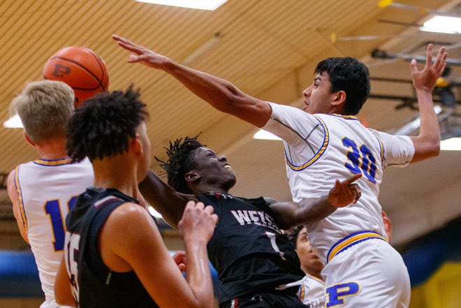 Weiss Wolves guard Titus Massaquoi, left, attempts the shot to the basket as Pflugerville Panthers guard Sahir Vohra defends during the fourth period at the District 18-5A boys basketball game on Dec. 20 at Pflugerville High School.