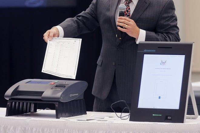 A representative from Smartmatic is shown in 2018 demonstrating his company's elections equipment. The voting machine company has threatened legal action unless Fox News and various Trump allies fully retract their baseless claims that the company helped flip the 2020 election for Joe Biden.