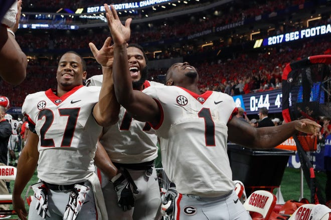 Former Georgia tailback Nick Chubb (27), offensive guard Isaiah Wynn (77) and tailback Sony Michel (1) celebrate on the sideline during the SEC Championship football game between Georgia and Auburn. Chubb and Michel were rewarded with a Rose Bowl victory and improved draft position after their return to Georgia during their season season. (AJ Reynolds for the Athens Banner-Herald)