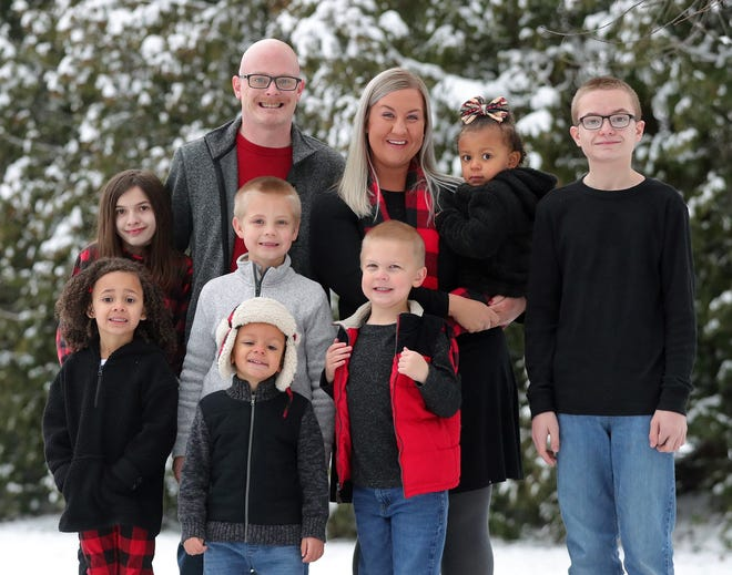 Drew and Melanie Cook-Montgomery's family grew when they adopted Lanie, Faith and Isaiah earlier this month. [Jeff Lange/Beacon Journal]