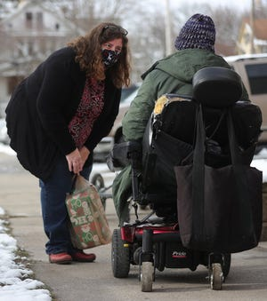 Lerryn Campbell, a volunteer at The Homeless Charity and Village, gives a Christmas gift to a homeless person Dec. 19 outside Middlebury Chapel in Akron.