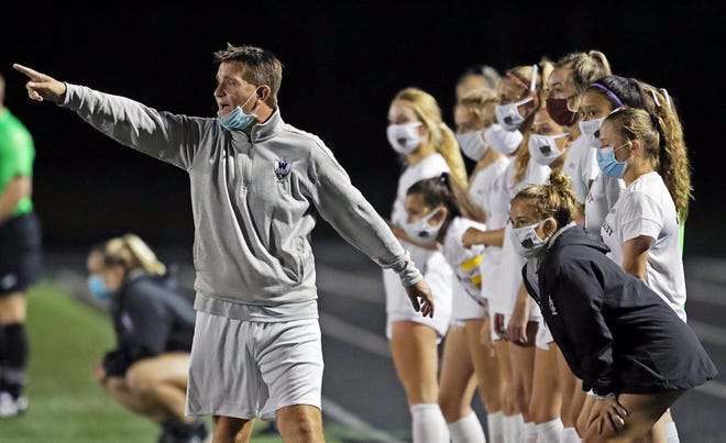 Walsh girls soccer coach Dino McIntyre, left, works the sideline during the second half of a soccer game at Brunswick High School in September. McIntyre is out as coach of the Warriors after an internal investigation revealed repeated violations of OHSAA rules. [Jeff Lange/Beacon Journal]