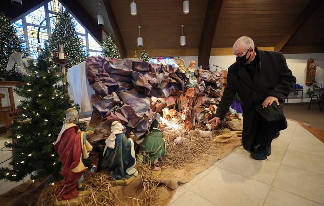 The Rev. David Durkee points out his favorite nativity scene on display at Queen of Heaven Catholic Church in Green.