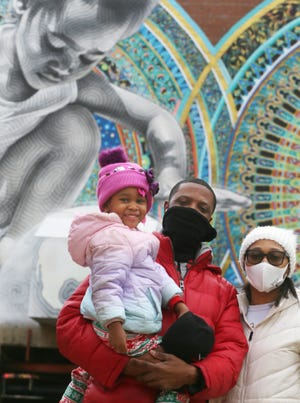 Monte Vales, 31, and his fiancee, Andrea Smith, 28, stand Wednesday in front of a Lock 4 mural with daughter Laila Giselle, 4, in downtown Akron. Laila's likeness was used in the artwork.