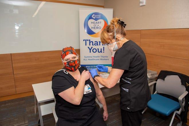 Summa Health ER nurse Sue Nollan receives a COVID-19 vaccine Wednesday.