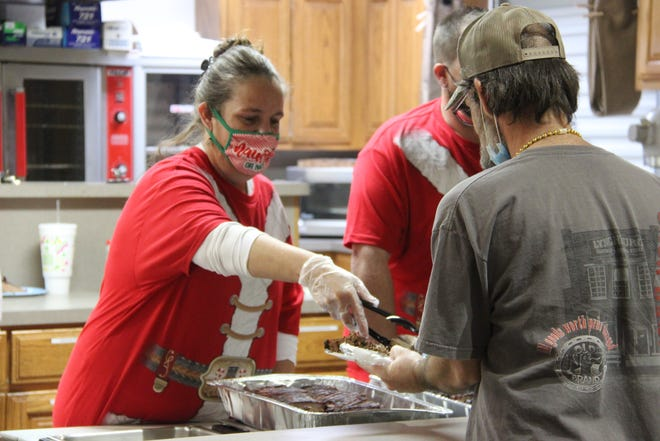 A woman serves food for drug court participants and their families at the program's second annual Christmas party.