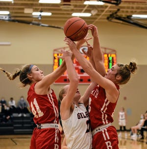 Ballard's Ashley Wuestenberg (left) and Molly Ihle battle Gilbert's Nessa Johnson for a rebound during the No. 3 (4A) Bombers' 39-33 victory over the No. 2 Tigers Dec. 22 at Gilbert.