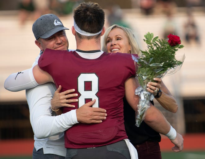 MBA's Zak Herbstreit (8) hugs his parents Kirk Herbsteit and Alison Butler during Senior Night ceremonies before their game against Briarcrest at Montgomery Bell Academy Friday, Sept. 11, 2020 in Nashville, Tenn.