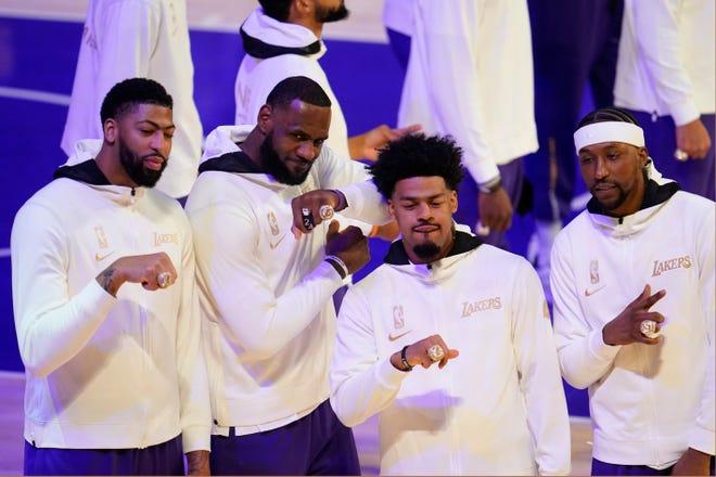 Los Angeles Lakers' Anthony Davis, LeBron James, Quinn Cook and Kentavious Caldwell-Pope show their championship rings before an NBA basketball game against the Los Angeles Clippers Tuesday, Dec. 22, 2020, in Los Angeles. (AP Photo/Marcio Jose Sanchez)