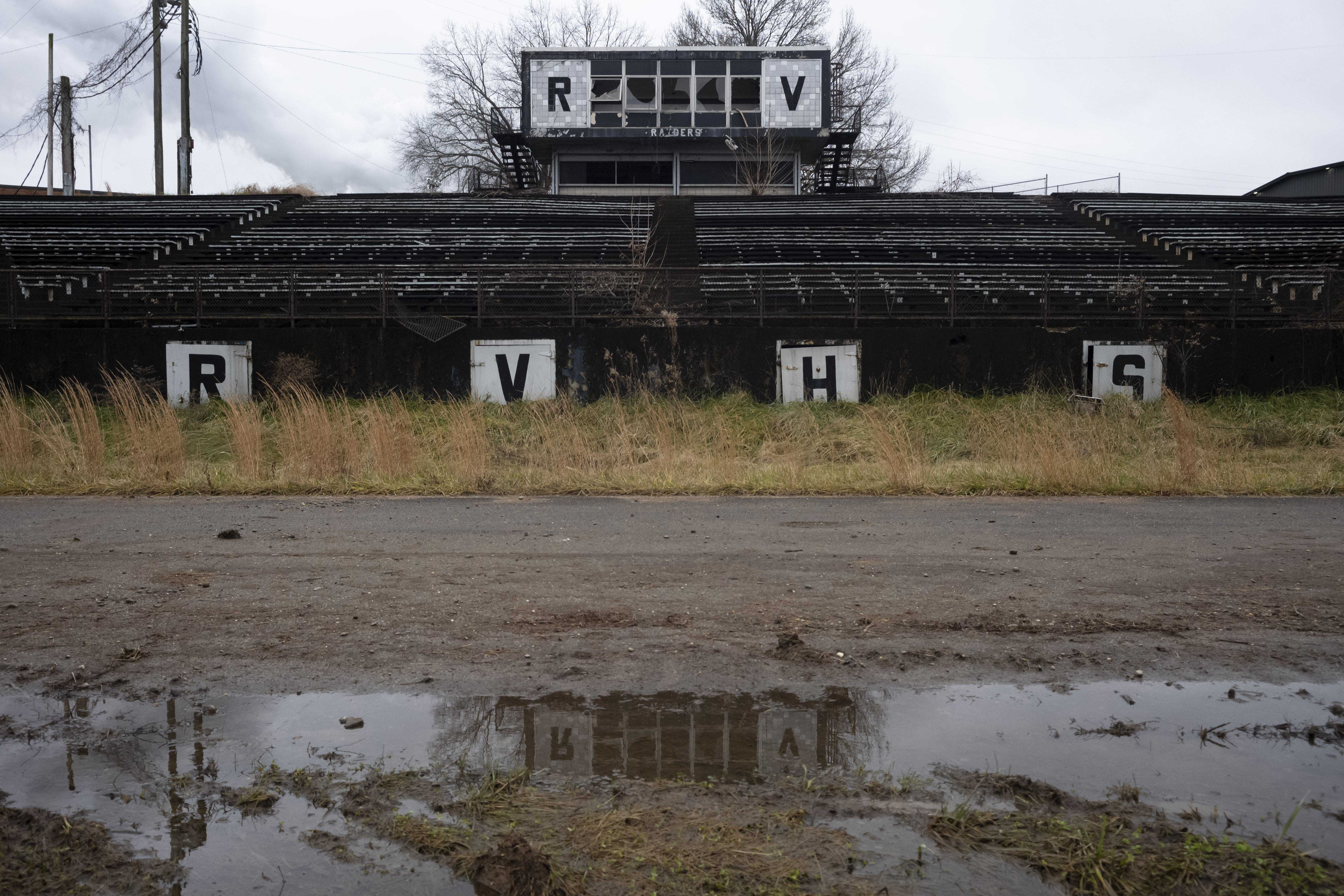 """The stadium stands of the former River Valley High School on Monday, Dec. 21, 2020 in Cheshire, Ohio, the site of a coal-burning power plant. Before residents moved away having been paid by American Electric Power, during sporting events, """"all the other schools would just complain so much because of the smell of the air that they had to run in,"""" a former student said."""