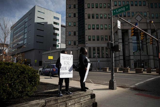 """Sasha Tutstone and her 9-year-old son, Jaelyn Berry, stand with signs reading """"Justice for Andre Hill #blacklivesmatter"""" and """"Cops Stop Killing Black People Our Skin is Not a Crime"""" in front of Columbus Police Headquarters Downtown."""