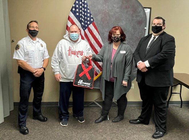 Dodge City police Capt. Shannon McGee; Susan Ratzlaff, MADD; and James Crux, assistant Ford County attorney, present police Sgt. Thad Brown special recognition for the Holiday Drive for Victims, remembering those killed or injured by drunk driving.