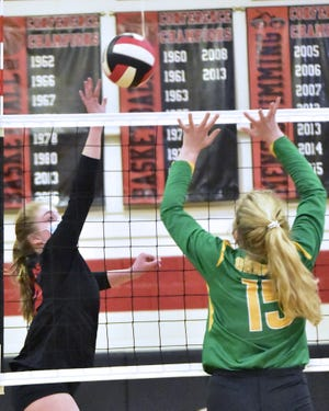 Central Davidson's Kayleigh Cranfill launches theball over the net while West Davidson's Sarah Johnson attempts to block Tuesday night at Central Davidson. [David Yemm for The Dispatch]