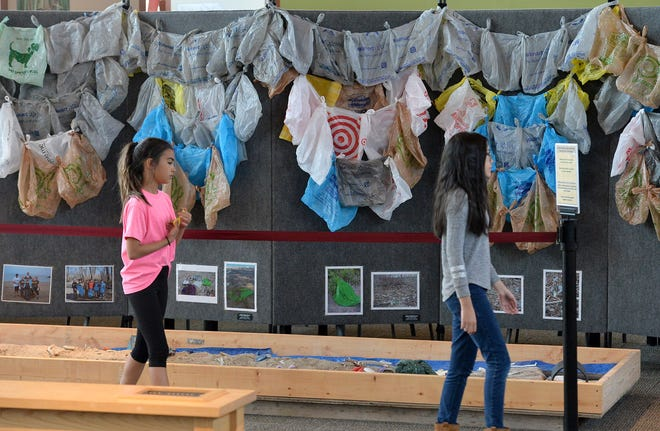 """In this file photo, Hannah Coletta of Erie and Jessica Cooper of Jacksonville, North Carolina look over an exhibit at the Tom Ridge Environmental Center in Millcreek Township in 2018. The exhibit, which features hundreds of plastic bags and is called """"Plastic Pollution Solution: One Small Change,"""" highlights the effects on humans, wildlife and the environment caused by plastic pollution in Lake Erie and other local waters. [CHRISTOPHER MILLETTE/ERIE TIMES-NEWS]"""