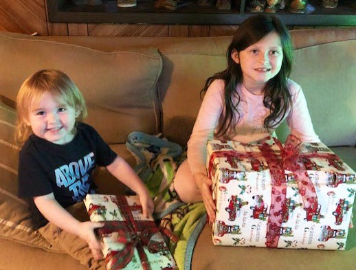 Siblings Cayden (left), 2, and Cylie, 9, celebrate early Christmas gifts Wednesday from Alan Pickert, a volunteer guardian ad litem who advocated for them in court during their foster care and adoption proceedings. They were in an unstable environment with their birth mother, but are thriving after being adopted.