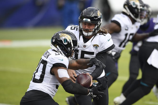 Jacksonville Jaguars quarterback Gardner Minshew II (15) hands off to running back James Robinson (30) during the first half of an NFL football game against the Baltimore Ravens, Sunday, Dec. 20, 2020, in Baltimore. (AP Photo/Nick Wass)