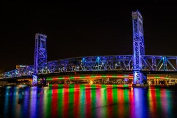 The Acosta Bridge's red and green light design reflects on the St. Johns River this week, complimenting the Main Street bridge's blue accent lighting.