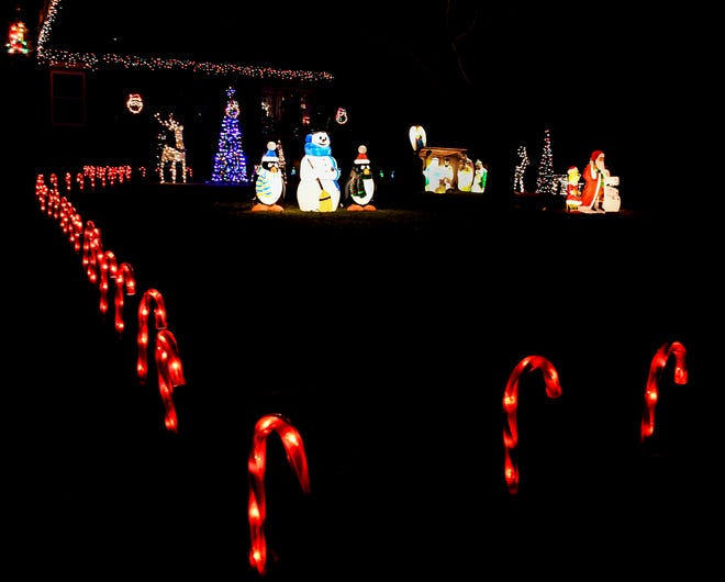 A variety of Christmas decorations decorate a yard in the 2200 blocl of North Third Street.  The scenes in the yard range from a nativity setting to a snowman with peguins to various lights on candy canes lining the yard to deer to trees and on the residence. {BRAD NADING/GARDEN CITY TELEGRAM]