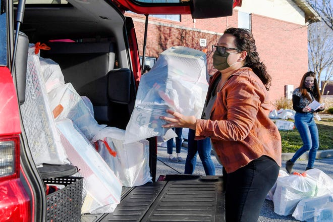 Genesis Lagos, a family advocate with Western Carolina Community Action, loads bags from Toys for Tots into her car Monday as she and her coworkers prepare to distribute the toys to families in the community.