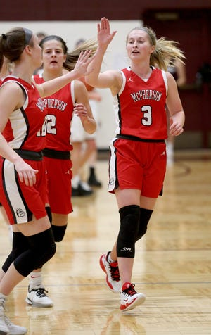 McPherson's Ella Schmid (10) left and Kassidy Beam (3) high five during their game against Buhler earlier this season. The Bullpups have now beaten Buhler twice — both times by more than 40 points.
