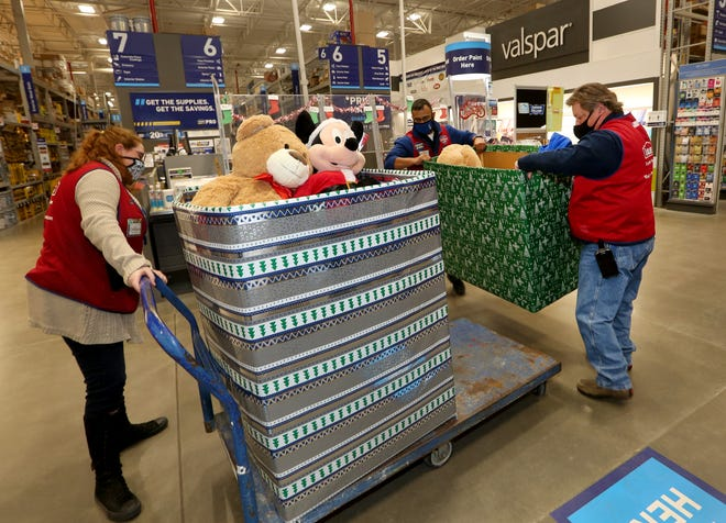 Colleen Dickey, left, Admin. Assoc., holds the cart still as Mike Delgado, Store Manager, back, and Sam White, Asst. Store Manager, right, load a second box of toys Wednesday morning at Lowe's, 1920 East 17th Ave.