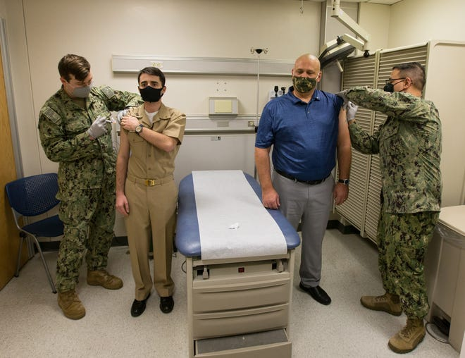 U.S. Navy Sailor LT. Anthony Bleyer Jr., a physician in the respiratory clinic, and Michael Labelle, a health benefits provider both assigned to Naval Health Clinic Cherry Point, receive the first Moderna COVID-19 Vaccine at Marine Corps Air Station Cherry Point, Dec. 23.