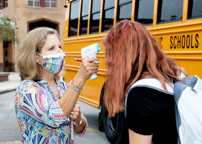 A Hunters Creek Middle School student has her temperature checked before heading to class on the first day of school in August 2020. Some parents want the Onslow County Board of Education to revisit its COVID-19 protocols for the 2020-21 school year as cases rise.