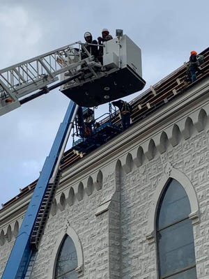Workers who were stranded on the roof of a South Peoria church are brought to safety by a ladder truck from the Peoria Fire Department on Wednesday, Dec. 23, 2020.
