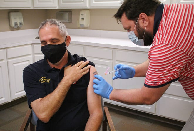 Newton Fire/EMS Chief Steve Roberson receives the first of two shots of a COVID-19 vaccine produced by Moderna. First responders received shots at the Harvey County Health Department as part of a phased rollout of the vaccine. Few area recipients reported side effects. [COURTESY IMAGE]