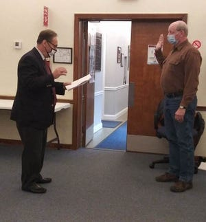 Christopher Scott, right, is sworn in to office as Silver Lake Village Council's new at-large member by Mayor Bernie Hovey at village hall on Monday, Dec. 21. Scott was appointed by council to serve in the post being vacated by Jerry Jones. (Submitted Photo)