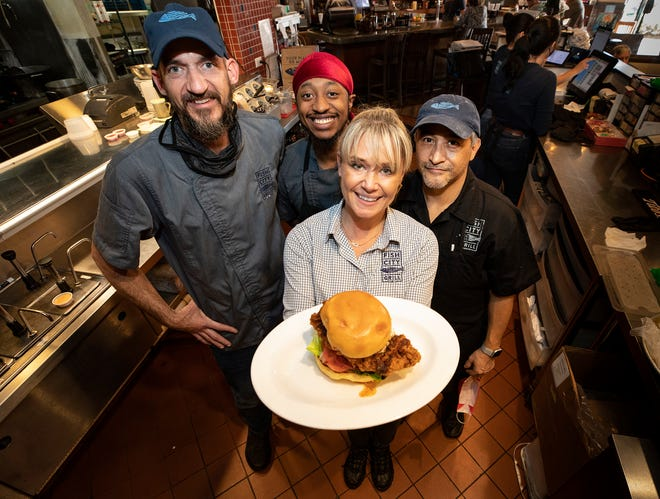 Sarah Ceretto, center, managing partner at Fish City Grill in Lakeland, holds the signature chicken sandwich with, from left, Bobby Arlington, Joel Moore and Juan Alvarez. Sarah's Hot Chicken is a virtual kitchen operating out of Fish City Grill.