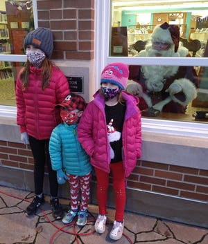 """Santa made a """"window stop by"""" at the Macomb Public Library to talk to children about their gift list. The Graham sisters Dehlia, Hattie, Mabel had their picture taken with Santa while practicing social distancing and wearing their masks."""