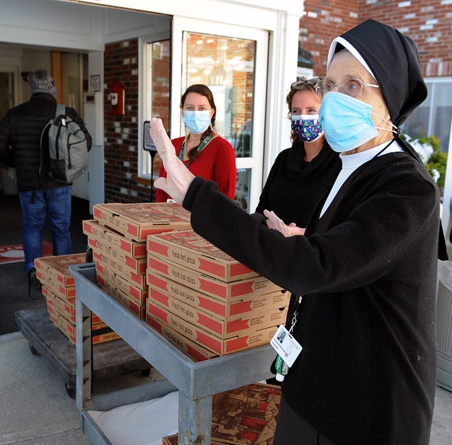 """Maureen McDonough, right, administrator at St. Patrick's Manor in Framingham, thanks Jake Binnall, not pictured, of Operation Goodwill & Cheer, a community mutual aid group, for delivering 25 pizzas from Zumi Pizza in Southborough on Wednesday, Dec. 23, 2020, as part of the """"Feeding Framingham's Frontline"""" campaign. Also pictured are Kelly Lincoln, left, and Assistant Administrator Michelle Luz."""