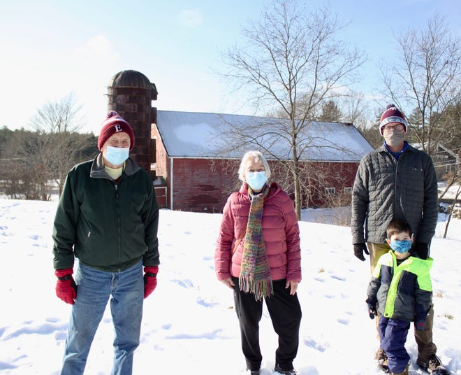 Exeter Conservation Commission members, left to right,  Bill Campbell, Sally Ward and Nick Campion, with his son Quinn, stand in front of Raynes Farm's historic barn. The Conservation Commission is hosting a scavenger hunt on Raynes Farm running through Jan. 3.