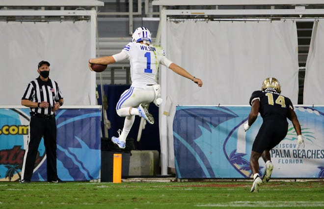 BYU quarterback Zach Wilson scores on one of his two touchdown runs against UCF Tuesday night in the Boca Bowl.
