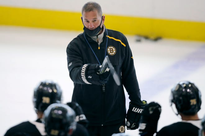 Boston Bruins head coach Bruce Cassidy talks with his players at the NHL hockey team's camp on July 14, 2020, in Boston. Cassidy will have to wear a mask behind the bench when he coaches in the upcoming NHL season.