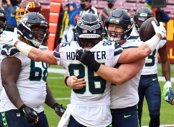 Seattle Seahawks tight end Jacob Hollister (86) is congratulated by guard Ethan Pocic after scoring catching a first-half touchdown pass in Seattle's 20-15 win over the Washington Football Team on Dec. 20. Seattle hosts the Los Angeles Rams on Sunday.