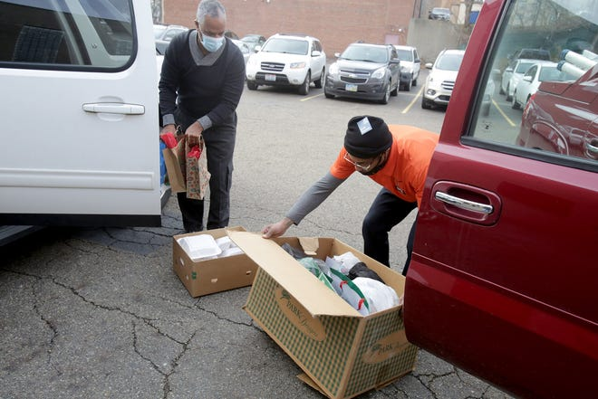 Friendship Baptist Church Pastor Reginald Hye (left) and Charles Danzy III prepare to deliver 55 hot meals and assorted gifts to the YWCA Canton homeless shelter in Canton. The home-cooked meal included ham, turkey, mashed potatoes and gravy, string beans and a roll.