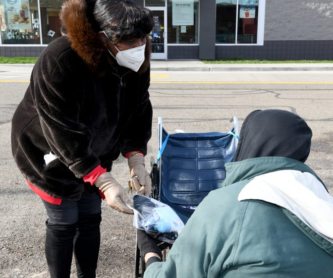 Audrey Walker passed out Christmas bags Wednesday in downtown Canton, part of her outreach Keeping Our Community Warm.