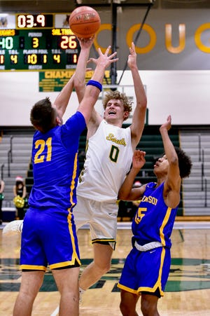 Salina South's Colin Schreiber (0) goes up for a shot while being defended by Hutchinson Myles Thompson (21) and Dauntary King (15) during Tuesday's game at the South gym.