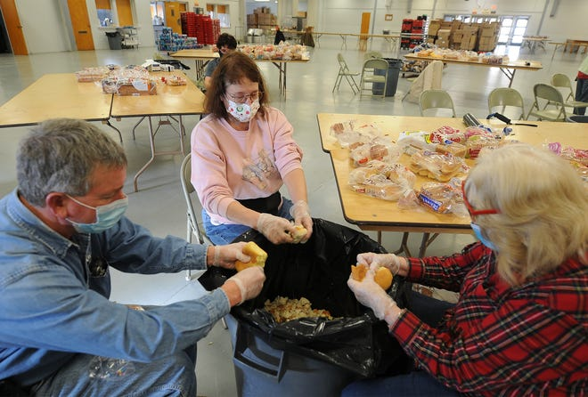 From left, volunteers Andy Phelps, of Dorrance, Susan Tuzicka and Barbara Williams break up bread into small pieces in preparation for making the turkey stuffing for the 38th annual Bill Fekas and Family Christmas Dinner.