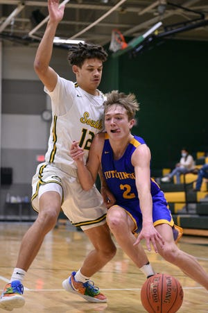 Salina South's Te'Jon McDaniel (12) defends Hutchinson's   Jake Huhs (2) during Tuesday's game at the South gym.
