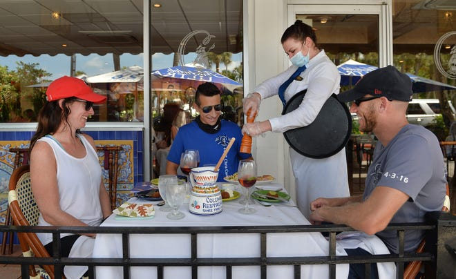 Newlyweds Kristy Clements, left and Gary Roose, right, of Tampa, met their friend Christopher Mouta, center, of Sarasota, for lunch at the Columbia Restaurant on St. Armands Circle in Sarasota on July 9, 2020. The Columbia opened this location in 1959.