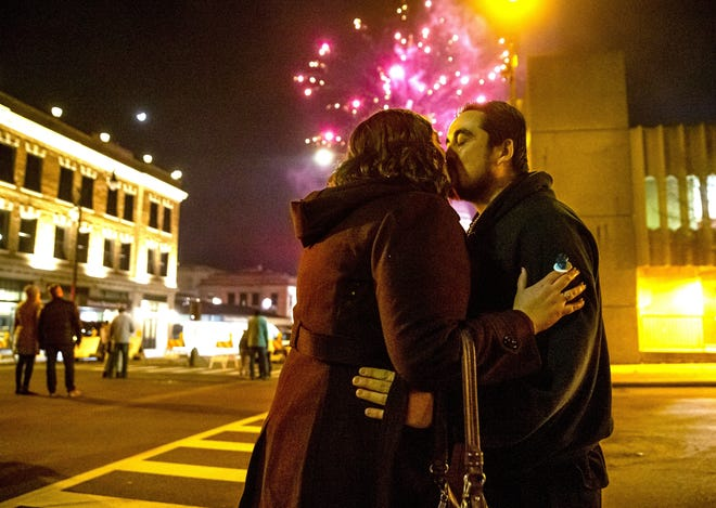 Fireworks explode over the Illinois State Capitol as Patrick Gillespie gets a kiss from his girlfriend, Kaitlin Kasper as she wears a candy ring that was used by Gillespie's son, Owen, to help him propose to her as the fireworks went off during the Springfield Area Arts Council's 33rd annual First Night Springfield New Year's Eve Celebration on Dec. 31, 2019, in Springfield. [Justin L. Fowler/The State Journal-Register]